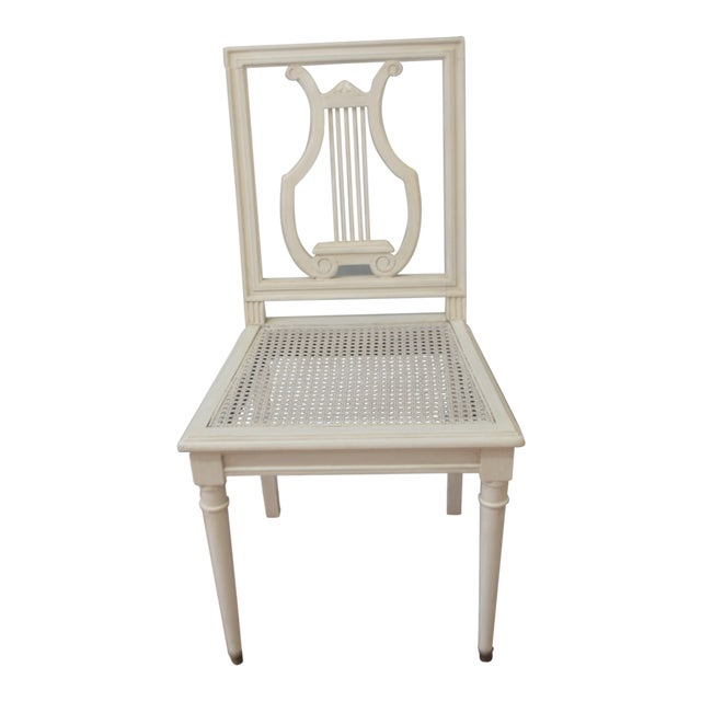 Set of charming Gustavian style painted lyre back chairs with caned seat. They are painted in a light cream color with...