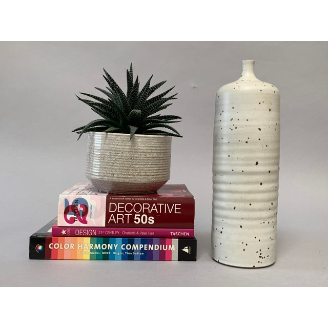 This tall studio-made vase features a subtly ribbed hand thrown cylinder form with a short narrow neck and an earthy white...