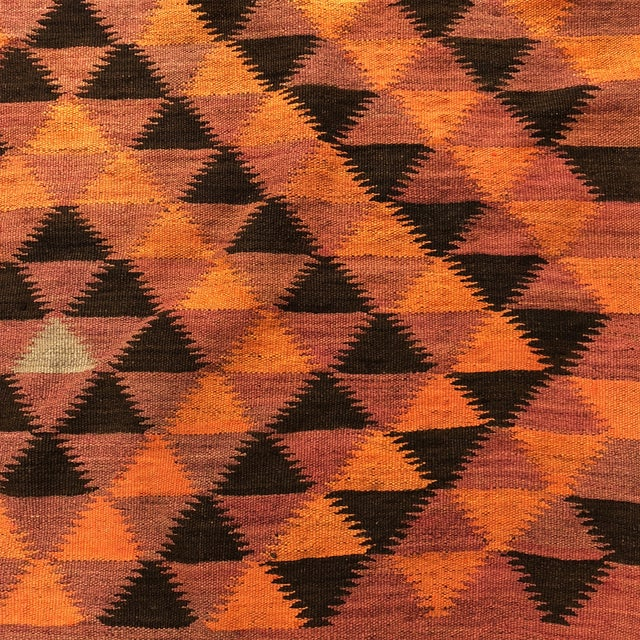 Stunning geometric pattern hand woven vintage kilim with earth tones and a pop of orangey pink. A few minor spots and one...