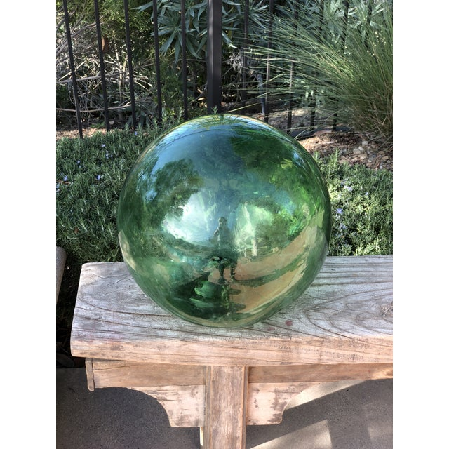 This oversized well traveled blown glass fishing float is a deep green and was used by fishermen off the coast of China....