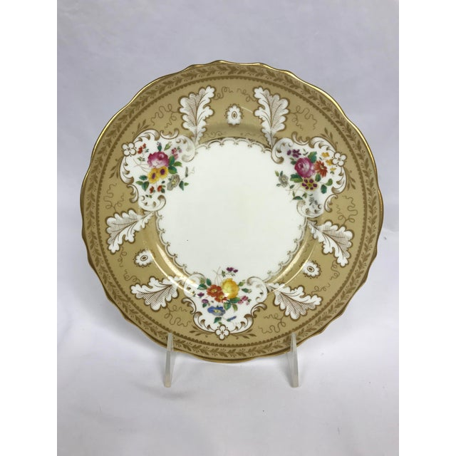 White ground. Gilt rim and decoration of stylized oak leaves over buff color. With three Rococo style reserves of hand...
