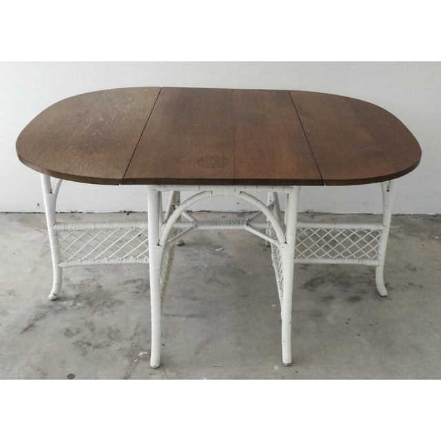 Antique white woven wicker base drop leaf dining table with oak wood top. Perfect for an informal breakfast table. Age...