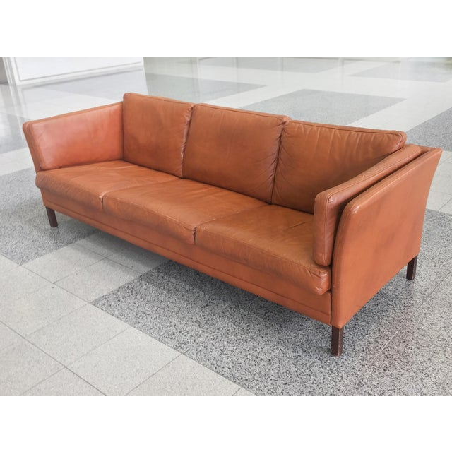 A handsome Danish Modern three-seat leather sofa produced by Mogens Hansen. The beautifully toned leather is in a warm...