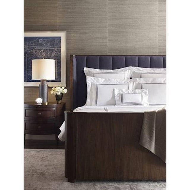 The Laucala Bed is a dreamy oasis of rich walnut veneer paired with striking upholstery channels on the inner headboard....