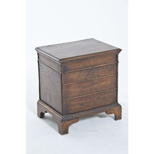 Antique box with hinged top and paneled sides.