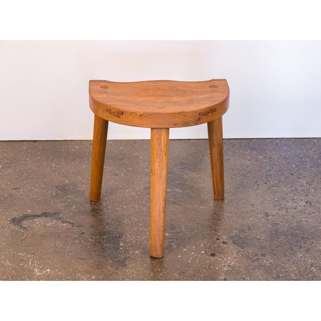 Three-legged 1950s Oak Stool designed by Jean Touret for Atelier Marolles. Beautifully carved demi-lune seat is sculpted...