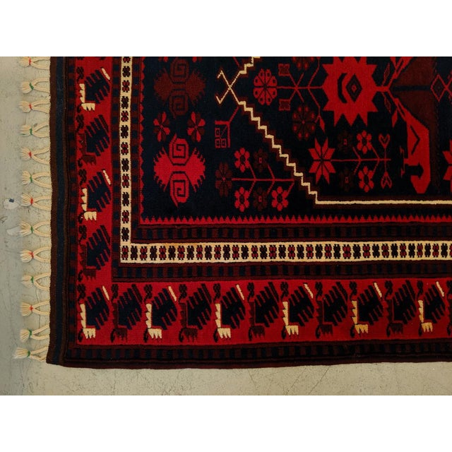 This is a beautifully hand-woven Persian rug, done in rich reds, deep navy blue, white and edging in black. The tassel...