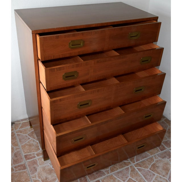 This is a Baker Furniture walnut campaign style chest of drawers. With countersunk brass handles and brass banding, the...