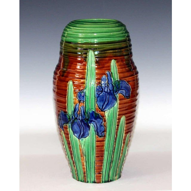 Awaji Pottery vase with blooming irises carved into accentuated throw ribs. The blue and green irises set aglow against...