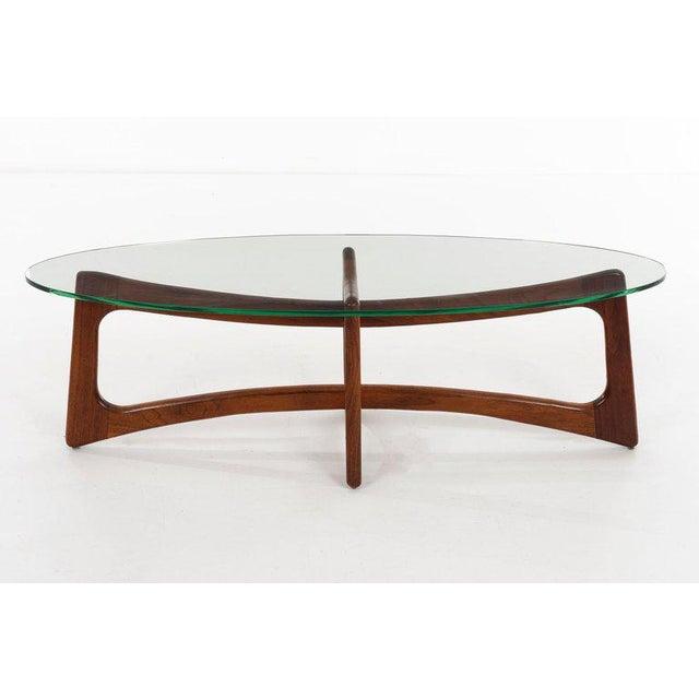 Adrian Pearsall (1926 - 2011) Model no. 2454-TGO Modernist oiled walnut cruciform coffee table with ovoid glass top....