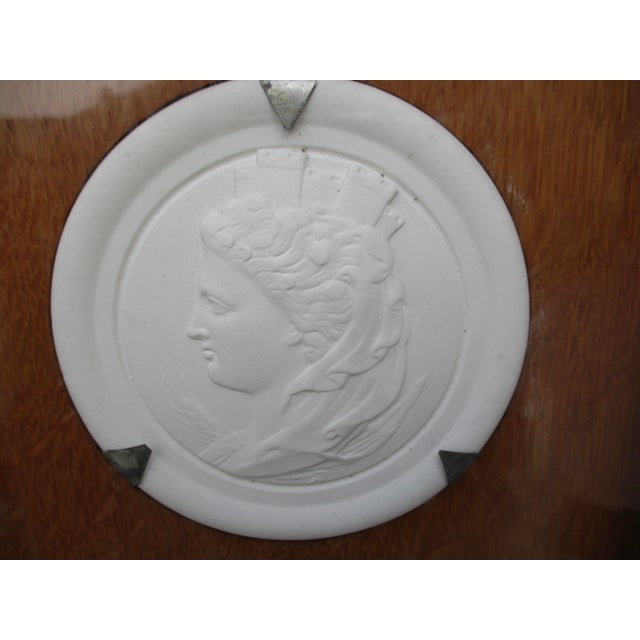 Bisque medallion of a classical female profile with fortress over her head. Encased in a solid oak frame and recessed...