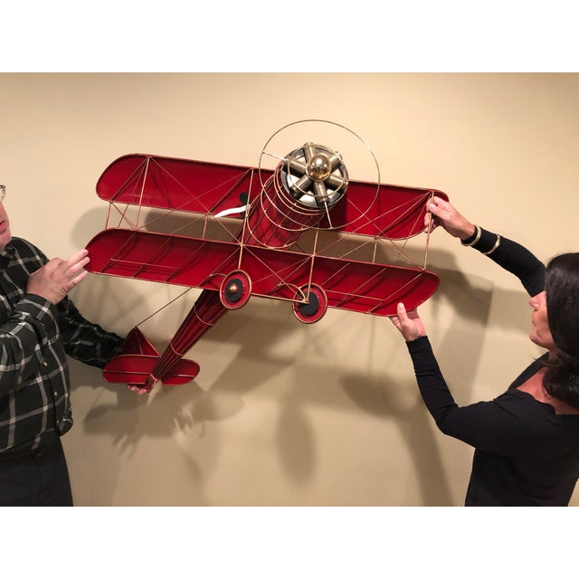 Super fun wall sculpture of a bright red prop plane with stylized pilot having scarf blowing in the wind. Signed C Jere 1987.