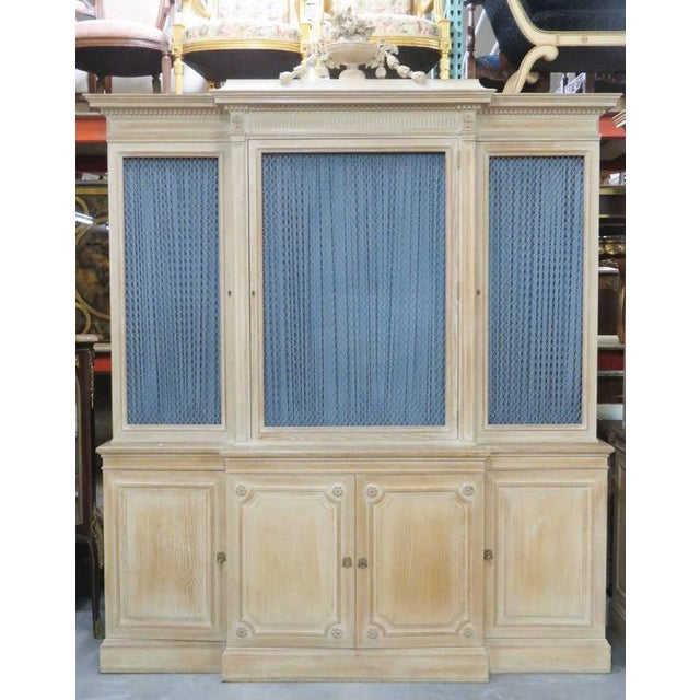 Stamped Jansen. Blond carved frame with carved urn crest and rosettes. Chicken wire front doors with blue curtains....