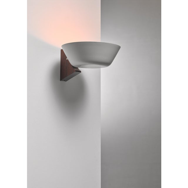 A mid-century wall lamp with a wooden wall-mount and a grey white lacquered bowl shaped metal shade.