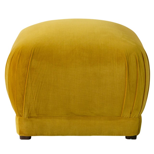 Smooth upholstery covers a sleek cushioned silhouette accentuated at the corners with delicate handcrafted pleating. The...