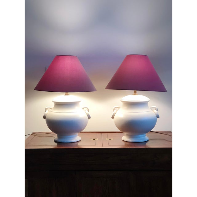 Beautiful white ceramic urn style lamps. Amphora form lends to transitional placement. Shades are for staging and not...