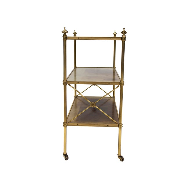 Petite leather-lined Brass etagere or bookshelf by Baker. The leather shelves are in a pale celadon and are stamped in...