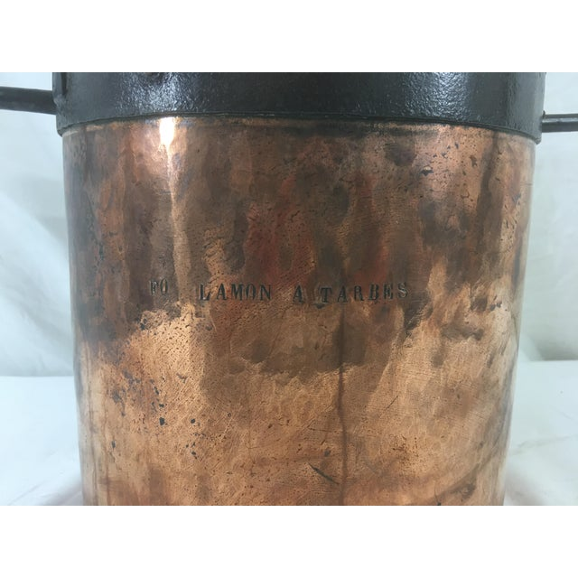 This large copper boiling pot has wrought iron banding and in engraved on both sides with it's chateau of origin. In good...
