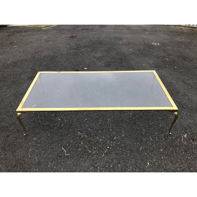 This 1970s glass topped cocktail / coffee table is framed in brass and has curved brass legs. Amply sized and in good...