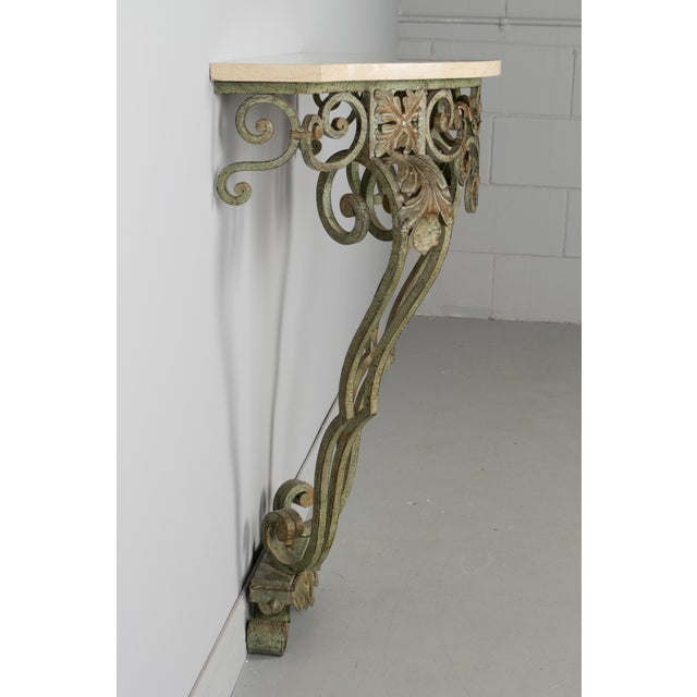 A French Louis XV style iron console with original verdigris painted patina and polished marble top. Circa 1940-1950.