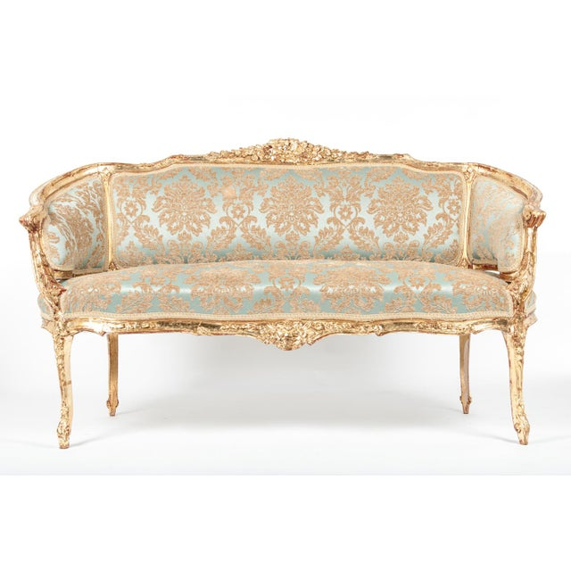 Antique gilded Louis XVI style settee with original frame. Excellent antique condition. Newly reupholstered. The settee...