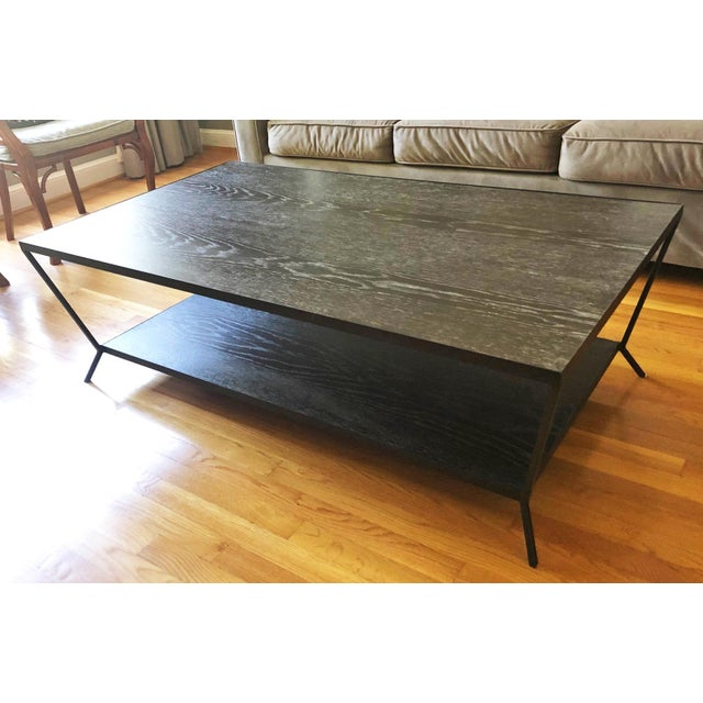 """Brand new Oly Sutter cocktail table in fumed oak finish and antique bronze iron base. Measures 54""""W x 30""""D x 17""""H."""
