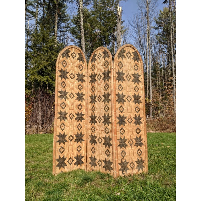 A mid-century, three panel, handwoven folding screen crafted of natural reeds and bound by fiber (instead of hinges)....
