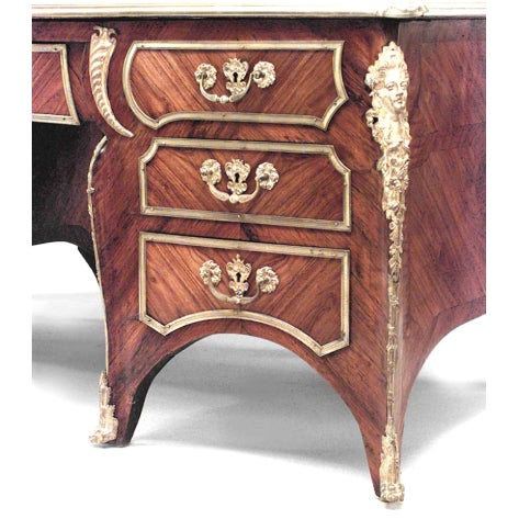 Nineteenth century French Louis XV style bronze-trimmed kingwood kneehole desk with a green leather top.