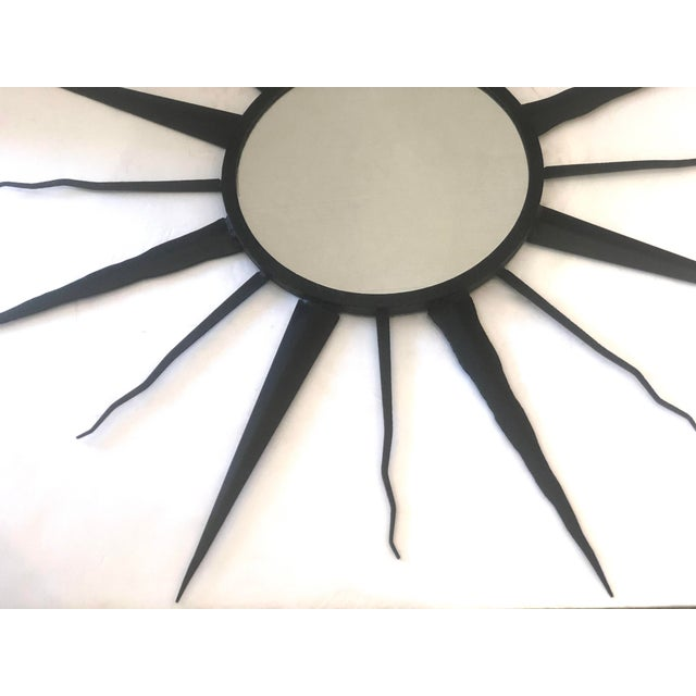 Unusual French C.1960 Black metal wall hanging Mirror by Chaty, Vallauris, France. This sunburst mirror, has a new mirror...