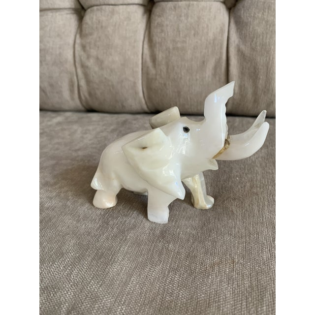 An elegant, playful sculpture of onyx in the shape of an elephant. Color is lovely, more white than many onyx stones which...