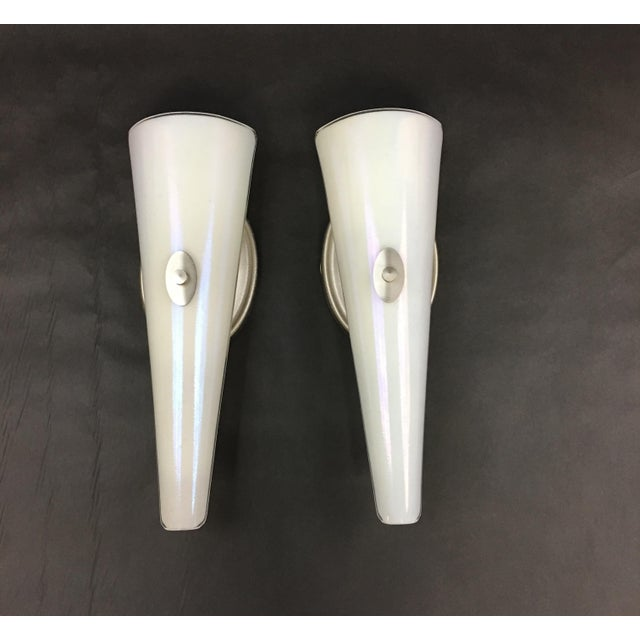 Pair of Neidhardt, Inc wall sconces. These sconces are finished in a silvery gold color sometimes referred to as...