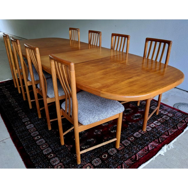 Danish Modern 1970s teak oval dining table with two removable leaves and custom protective pads. Set includes eight...