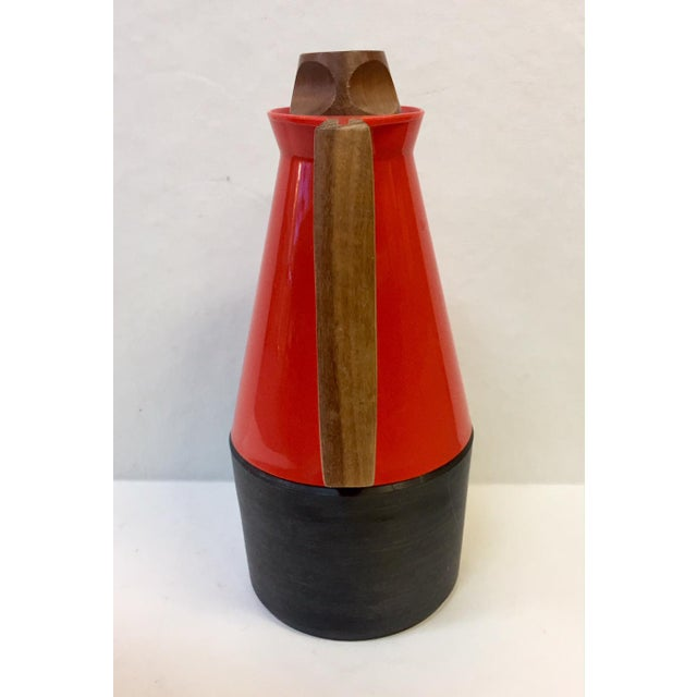 Beautiful carafe pitcher with classic mid-century teak and red/orange and dark gray plastic features.