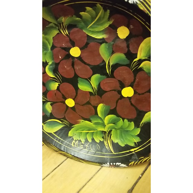 Here's a very pretty folk art hanging plate that was created in Mexico several years ago. It features maroon flowers. The...