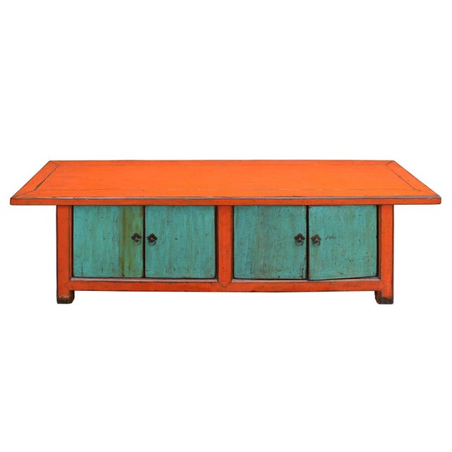 This is a wooden low cabinet with distressed orange color frame and light blue color on four doors. It is good as a TV...