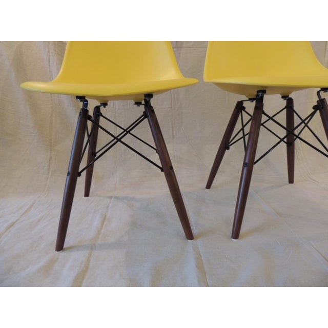 Pair of Eames Style Yellow Molded Plastic Side Chairs The bent wire provides a strength to the legs to finish a...