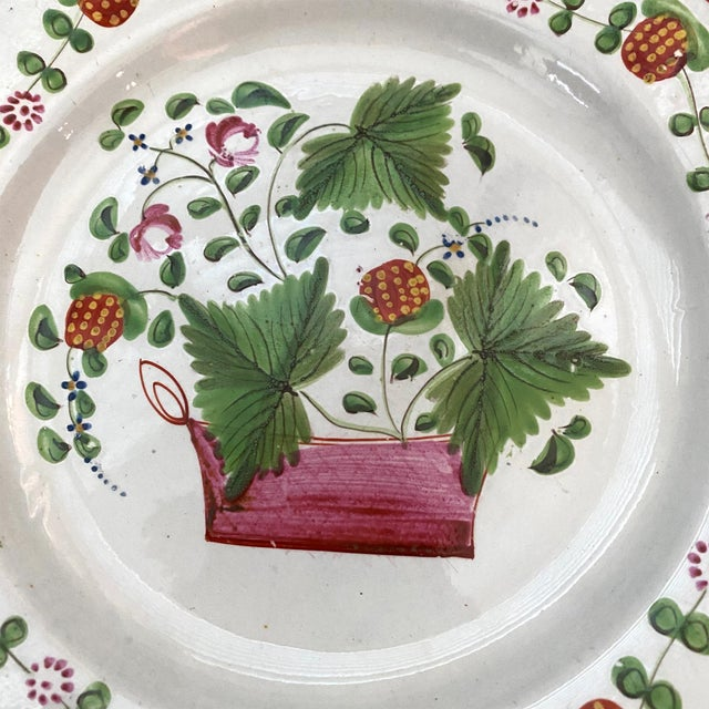 A fine English early 19th-century soft paste porcelain plate decorated with a band of strawberries on the edge surrounding...