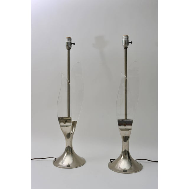 This pair of late Mid-Century Modern Lucite and polished chrome table lamps were designed and produced the American light...
