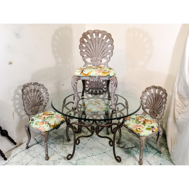 This vintage patio set has four grotto style cast aluminum chairs with new indoor / outdoor shell motif fabric. The glass...
