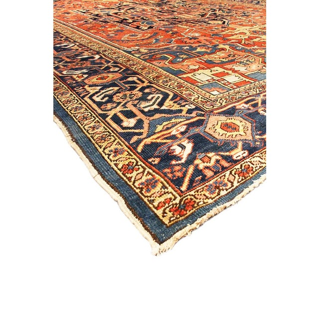 An antique hand-knotted Heriz rug with a geometric medallion motif on a rust field. Some age appropriate wear gives the...