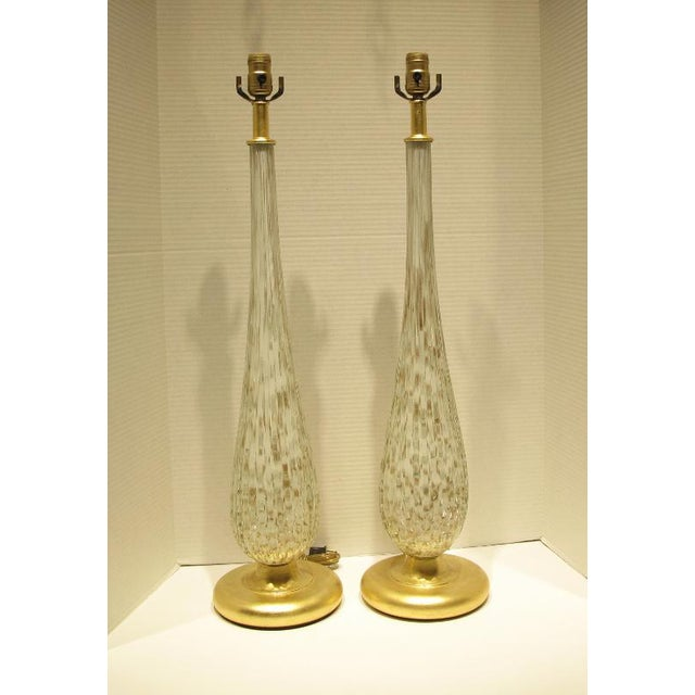 Large vintage matched pair of Murano glass lamps with white and gold flecks. Made in the 1960s in Italy. The lamps have...