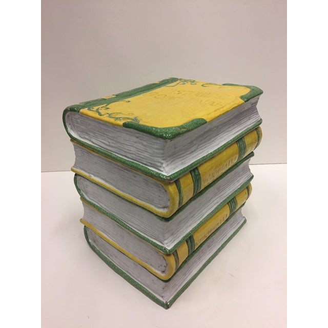 A beautiful and unusual glazed terracotta garden seat in the form of a stack of books. Colors are a snappy white, yellow...