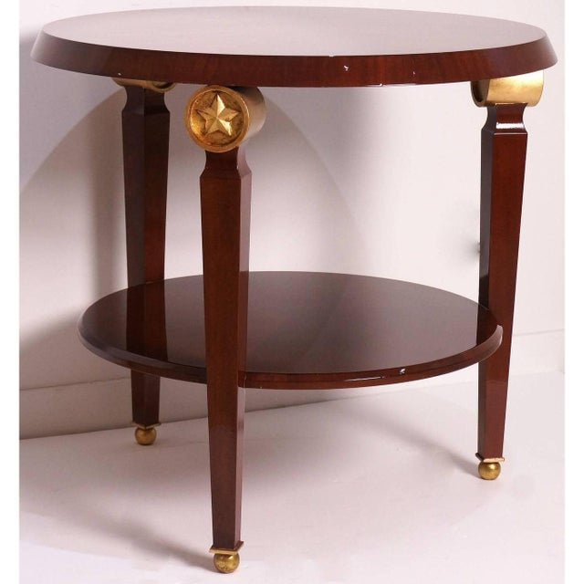 This two-tiered center-table inspired by Maison Jansen, with its gold-finished star medallions, mahogany wood veneers and...
