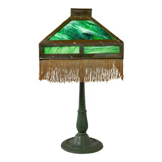 1920s Cast Iron Art Deco Table Lamp With Brass and Slag Glass Shade Trimmed With Tassel Fringe For Sale