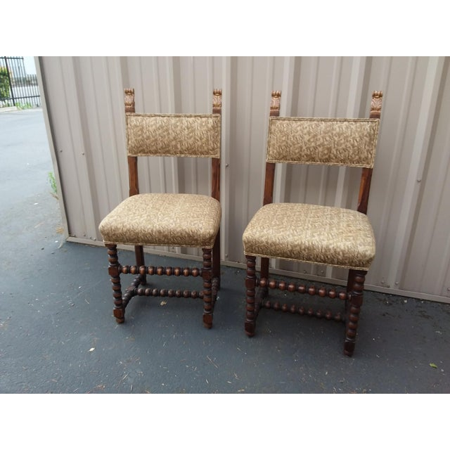 Pretty pair of antique chairs with Gilt wood accents and fortuny fabric upholstery.