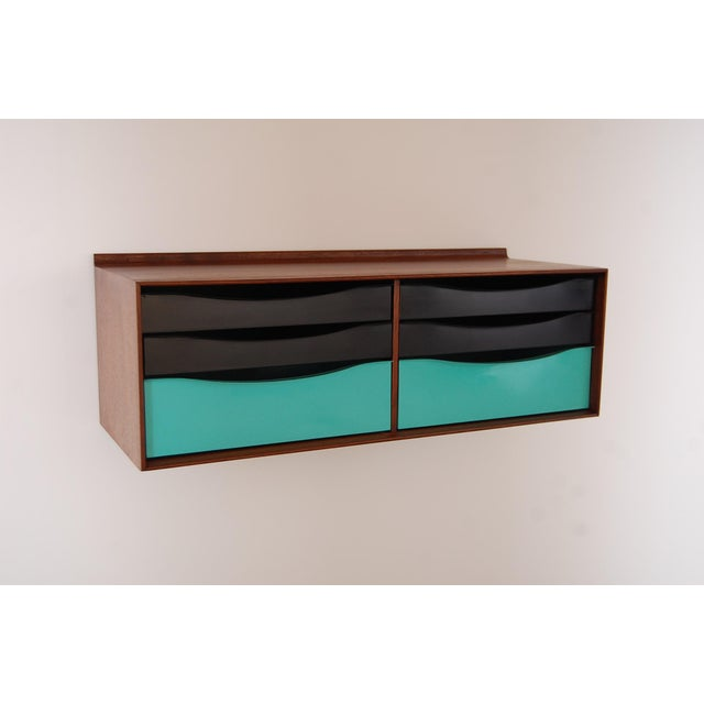 Modernist six drawer wall hanging cabinet in walnut and metal, circa 1964. Case is constructed of walnut, and drawers are...