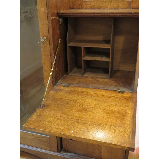 Solid Oak Curio Cabinet replete with glass display area and writing desk. There are holes and some fixtures inside the...