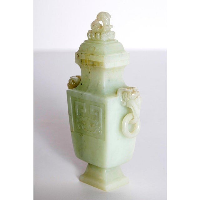 A pale celadon Chinese vase and cover carved front and back. Twin ring handled elephant heads at sides. Cover has a...