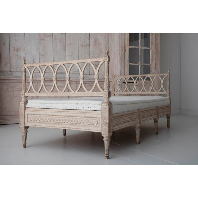 A beautifully carved Swedish Gustavian Style freestanding daybed newly upholstered in hand-stiched linen. The sides are...