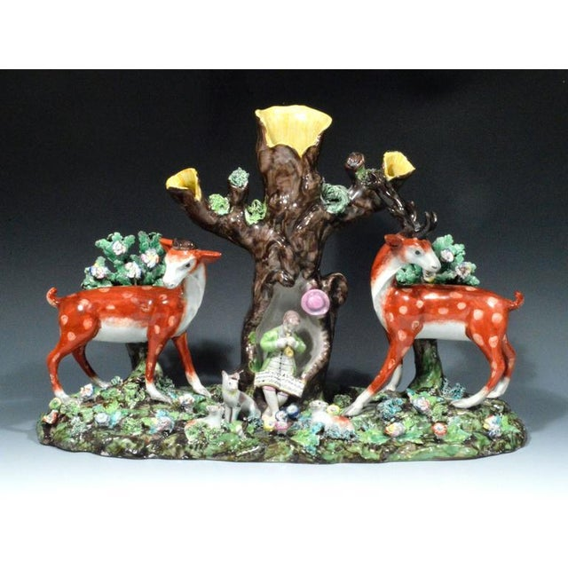 This remarkable rare Staffordshire pearlware large group depicts two large figures of a stag and doe facing each other...